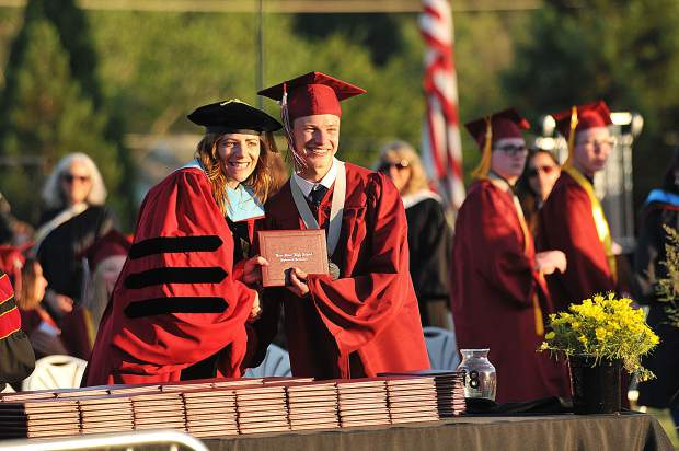 Bear River Principal Amy Besler smiles and poses for pictures with graduates as she hands them their diplomas.