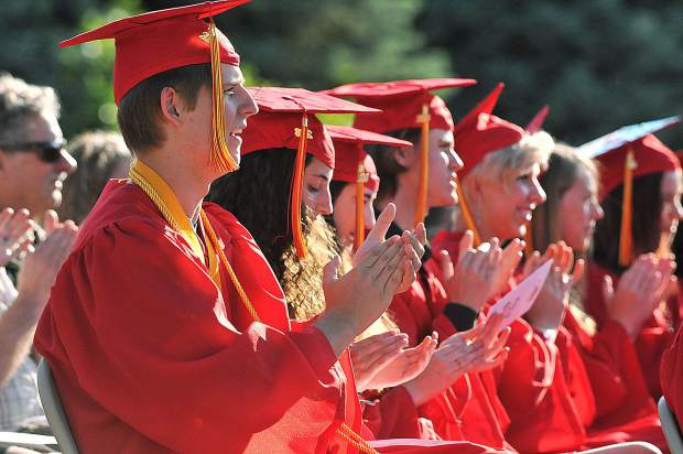 Miles Gregory Mason (left) applauds principal Noah Levinson following his faculty address during the 2018 Ghidotti Early College High School graduation.