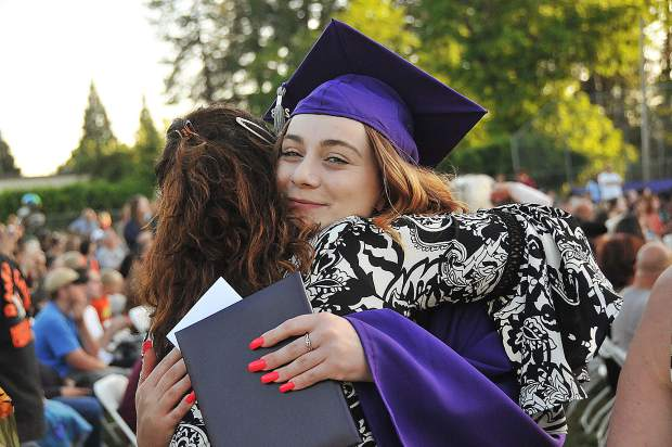 2018 Silver Springs High School graduate Katriena Mulligan smiles as she hugs a school faculty member during Thursday evening's graduation ceremony.