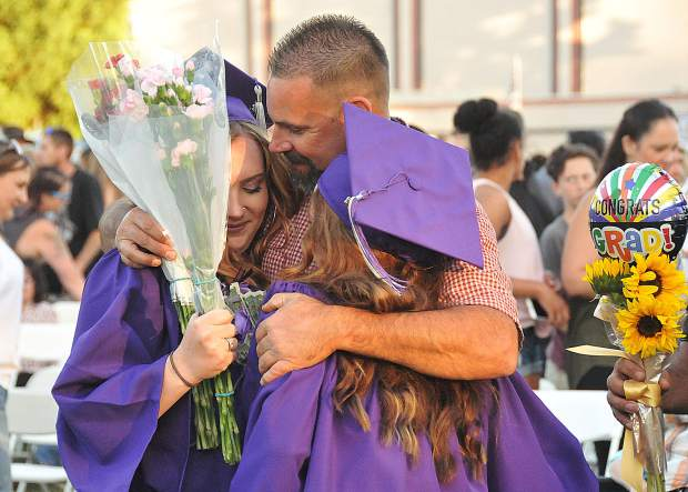 A parent gives a large embrace to two graduates following Thursday evening's Silver Springs graduation ceremony.
