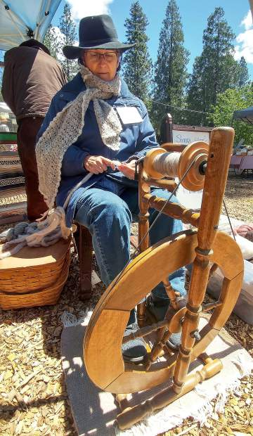 Barbara Engle, who runs Sierra Wools out of Penn Valley, uses a traditional spinning wheel to spool her wool that she has for sale at the grower's market.