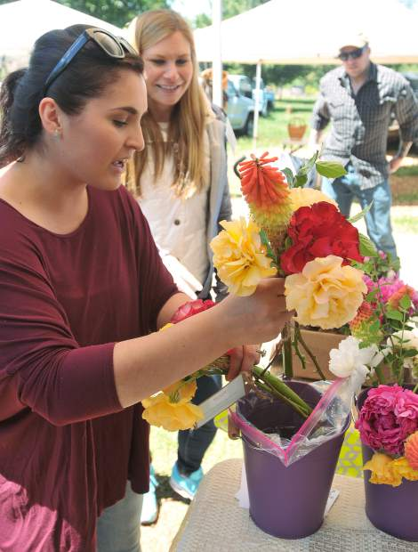 Denali Fickus (left) selects a bouquet of fresh cut flowers from The James Ranch's Laura Columbel (right) during a Nevada County Grower's Market in this archive photo.