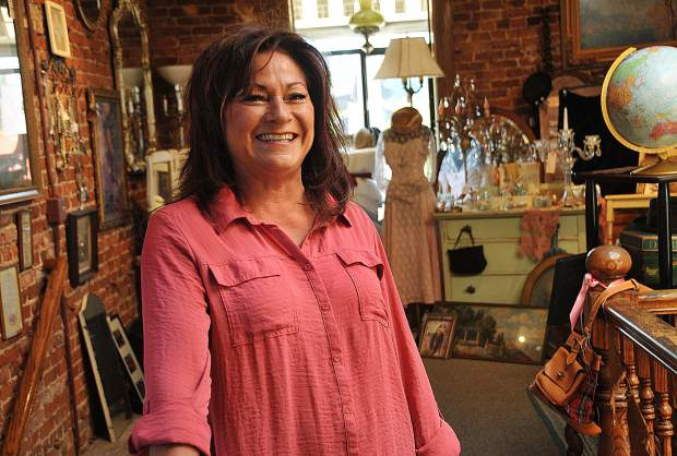 Vintage on Main owner Susan Escano smiles from the second floor of her downtown Grass Valley antique store. Escano's regular customers compliment her eye for eclectic finds and enjoy adding pieces to their own collections.