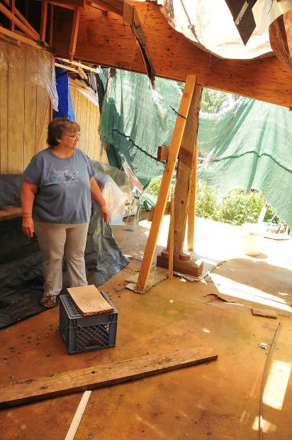 Creekside Village mobile home resident Barbara Magliocca stands in the tattered remnants of what used to be the living room of her and husband Ralph's mobile home in Penn Valley after an oak tree came crashing through in April of 2017. After waiting for repairs for more than a year, management want's them out.