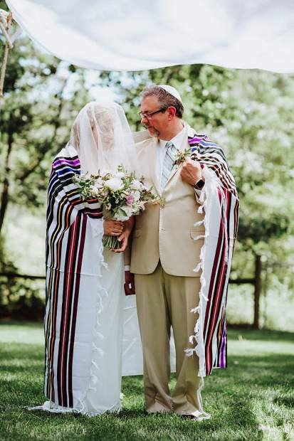 Karen Nathanson and Mark Gold stand under the chuppah, wrapped in Mark's prayer shawl, during their wedding ceremony June 2.