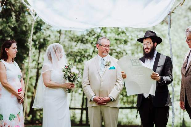 Rabbi Nochum Yusewitz performs a traditional Orthodox wedding ceremony for Mark Gold and Karen Nathanson under a chuppah on June 2. Here, he is seen reading the ketubah, or marriage contract, which is written in Aramaic.