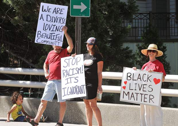 Spectators hold signs to support those riding against racism Friday evening in Nevada City.