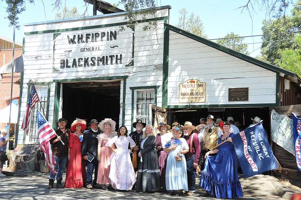 The cast of the Rough and Ready Rascals poses for a picture in front of the historic Fippin Blacksmith shop in downtown Rough and Ready following their yearly performance of The ongoing saga of Rough and Ready Sunday at Secession Days.