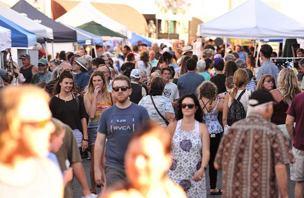 Thursday Night Market goers fill the streets around the intersection of Mill and Main streets where arts, crafts, and various other vendor booths offered their wares for sale.