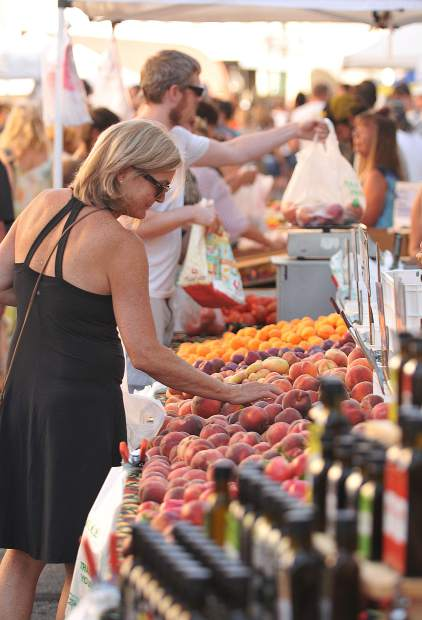 A shopper looks for the perfect fruit from one of the many farm stands available during Thursday Night Market in downtown Grass Valley.