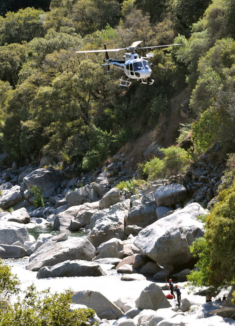The CHP helicopter utilizes a winch to hoist up the body of Tuesday's drowning victim on the South Yuba River, just downstream of the Highway 49 bridge.