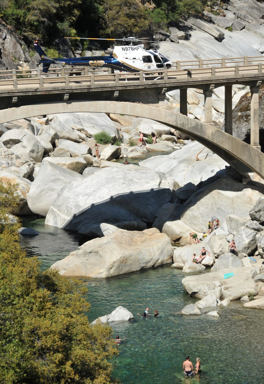 A CHP helicopter waits to aid in the recovery of Tuesday's drowning victim while others enjoy a hot day in the cool water of the South Yuba River.