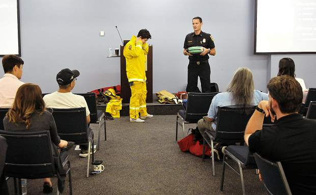 Cal Fire PIO Jonathan Cox demonstrates the gear used by wildland firefighters with the help of Sacramento Bee breaking news reporter Julia Sclafani during a recent media training.