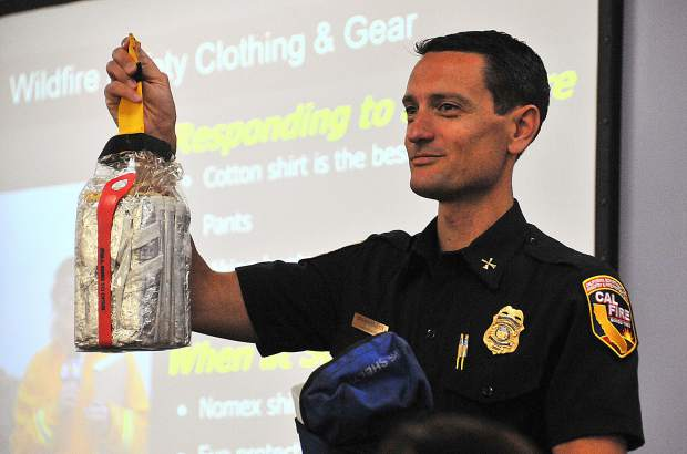 Jonathan Cox, Cal Fire Battalion Chief and Public Information Officer for Northern California, holds up a wildland firefighters last line of defense, the fire shelter, during a recent media wildfire training at the Sacramento Bee.