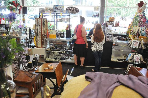 A pair of shoppers come to the counter after perusing the selection of the Women of Worth thrift store in Nevada City.