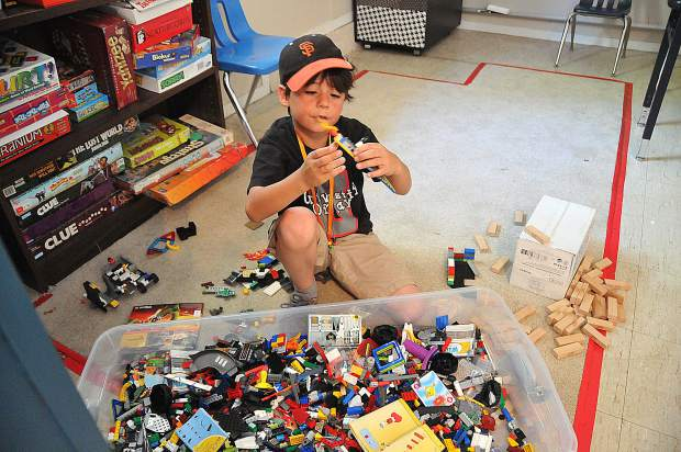 Mateo Saldana, 9, enjoys playing with a large tub of Legos during camp Friday in Grass Valley.