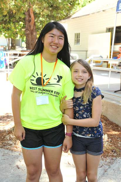 Camp counselor in training Mei Douros gets a hug from little leader in training, nine year old Shiloh McHone.