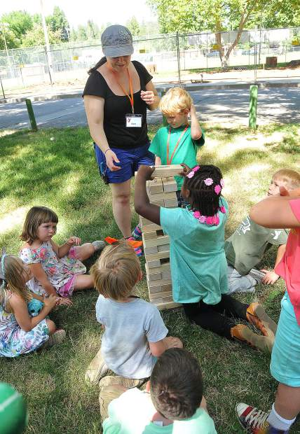 Gold Country YMCA camp counselor Cori Ove assists a group of participating children with a game of jumbling towers during Friday's camp.