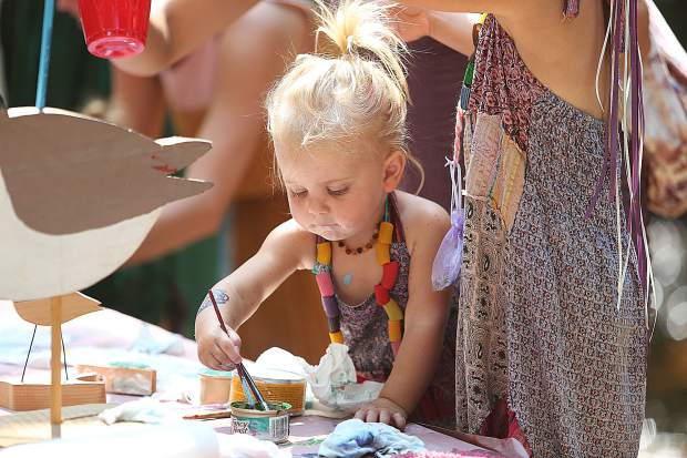 Two year old Bennett Minnor pays close attention to her painting work at the Childrens Festival Friday.