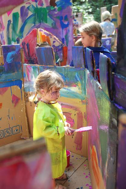 Two year old Melina Morey assesses her painting work on that she's applying to the Dragon Castle, a cardboard maze where Childrens Festival attendees can paint and get messy to their hearts' content.