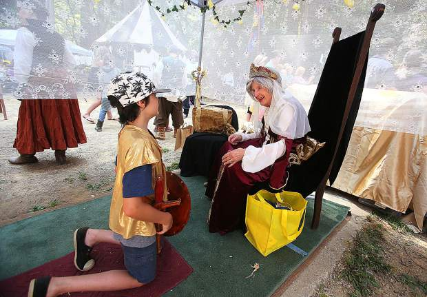 A Childrens Festival goer is knighted by the fair Queen Elizabeth of the event.