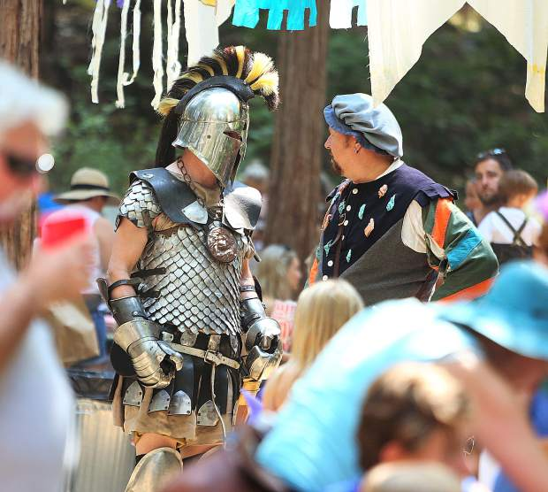 A knight in shining armor and another medieval character exchange words among the participants of Friday's Childrens Festival.