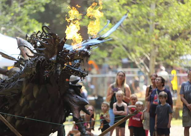 A metal fire breathing dragon captivates the imagination of those young and old at Friday's Children's Festival.
