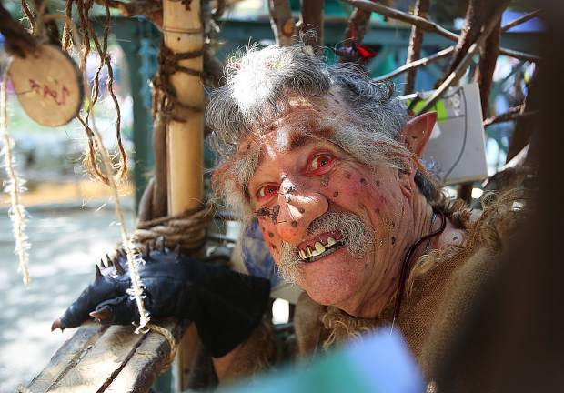 The Blue Ogre of the Troll Booth shows his toothy grin while waiting for the youngsters of the Nevada City Children's Festival, to pay his toll to cross Little Deer Creek Friday morning in Pioneer Park. His toll payments range between dried leaves, sticks, and pinecones.