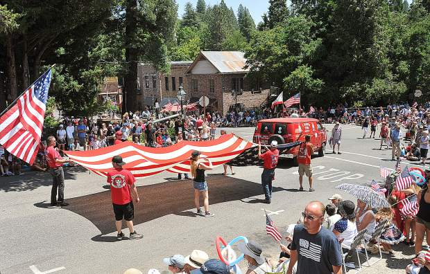 A large showing of Clampers from the Nevada City Chapter of E.Clampus Vitus hold a large United States Flag as they march down Broad Street in the Independence Day Parade.