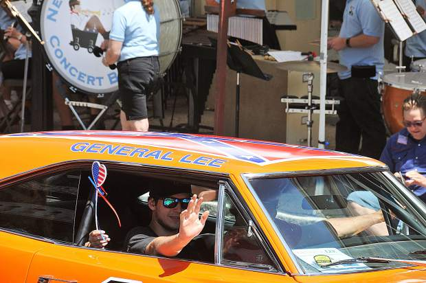 The drivers of the General Lee wave to fans during Wednesday's Independence Day parade from the inside of a 1969 Dodge Charger in downtown Nevada City.