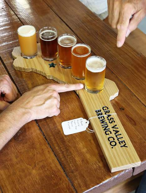 A pair of customers decide which of Grass Valley Brewing Company's many brews to try first as they choose from a flight tray shaped in the outline of Nevada County.
