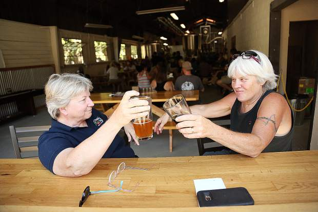 Suzanne Fellows and Sandy Lindblad cheers each other from the open air seating located adjacent the entrance of the brewery portion of Grass Valley Brewing Company following Thursday afternoon's opening day of business.