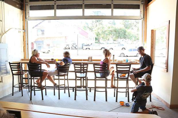 Folks sit next to the open air of Grass Valley Brewing Company's brewery now open in downtown Grass Valley.