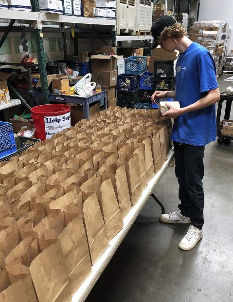 Food Bank of Nevada County volunteers, including (from left) Niko Coonen, Eva Cheever, Caitlin McCormick and Dan Parker, distribute a lunch from the free Summer Lunch Program to Nevada County youth last week in the Glenbrook Basin.