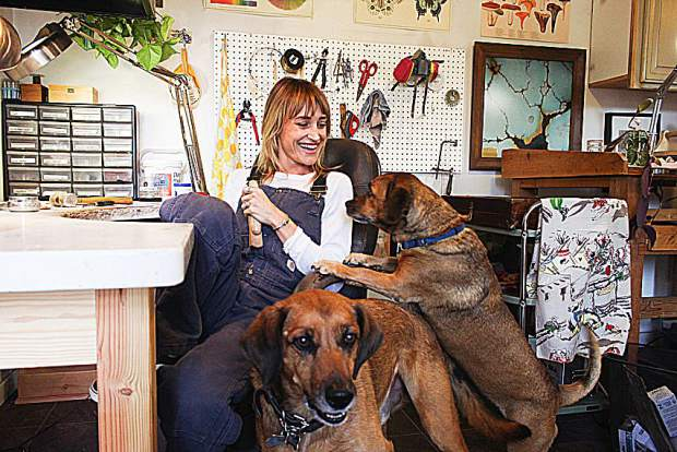 Leora Coronel, owner of Gather Jewelry, plays with her dogs in her home studio in Nevada City. Learn more at GatherJewelry.com.