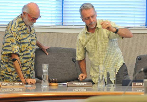 Recently re-elected Nevada City Councilmember Duane Strawser (right) removes himself from the mayor's seat as newly selected Nevada City Mayor David Parker takes the helm at the beginning of Wednesday's city council meeting.