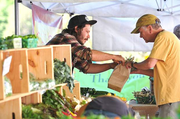 Fog Dog Farms' Will Holland helps a customer with his selection during Saturday's Nevada City Farmer's Market.