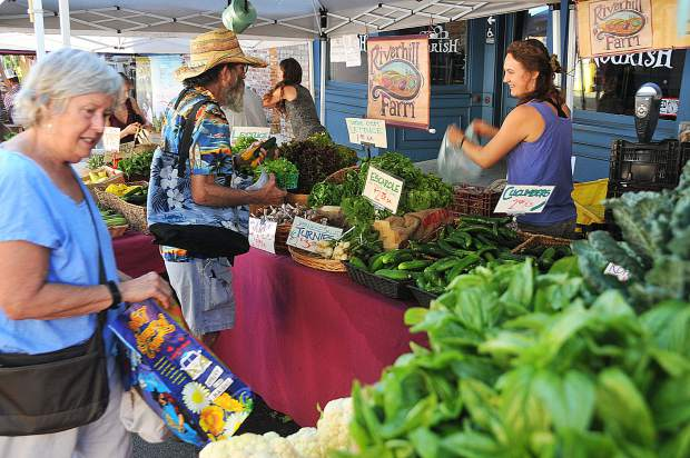 Folks check out Riverhill Farm's veggie stand on Union Street.