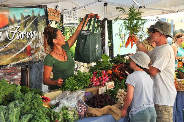 Shoppers pick their selections from First Rain Farm, based out of Nevada City, during Saturday morning's Nevada City Farmer's Market.