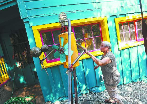 Davis inspects one of her metal sculptures placed outside of her brightly painted Boulder Street Victorian home.