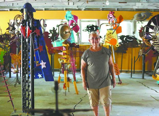 Ginny Davis stands in her workshop where many of her metal creations are made and displayed.