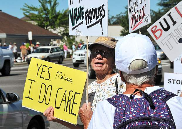 A woman holds a sign that reads, 'Yes Melania I do care' during Saturday's demonstrations at the intersection of Brunswick and Sutton Avenue.