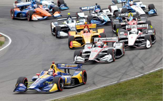 Alexander Rossi (27) leads the field through a corner at the start of the IndyCar Series auto race, Sunday at Mid-Ohio Sports Car Course in Lexington, Ohio. Using a two-stop fuel strategy, Rossi led 66 of the race's 90 laps to earn his second win of the season.