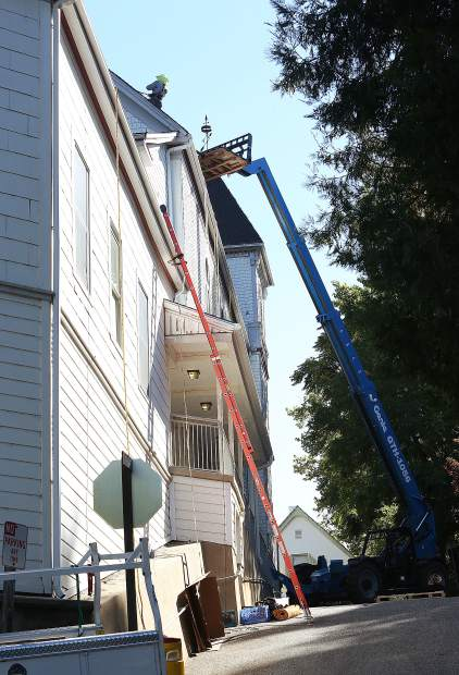 Construction crews from Sustainable Energy Group, utilize the help of a large forklift, to hoist the solar panel arrays into place atop the Nevada City United Methodist Church Wednesday.