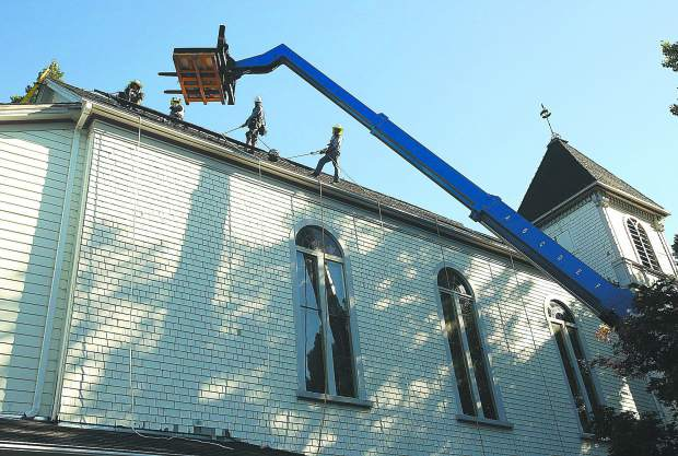 Work crews from Nevada County based, Sustainable Energy Group, scale the top of Nevada City United Methodist Church Wednesday morning, to install a solar panel array that will cut the church's energy consumption by 75%.