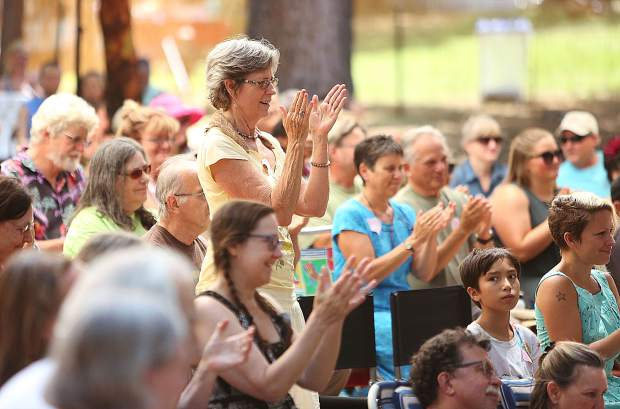 Festival goers applaud a well-told story during Saturday's festival lineup at the North Columbia Schoolhouse's outdoor amphitheater.