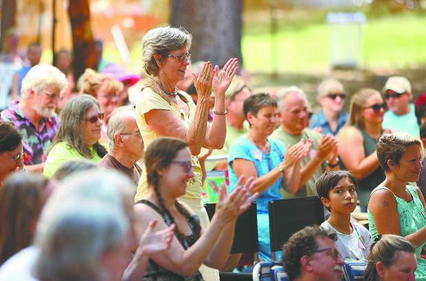 Festival goers applaud a well told story during Saturday's festival lineup at the North Columbia schoolhouse's outdoor amphitheater.