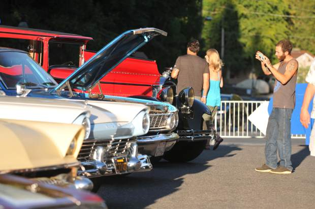 Auto enthusiasts take photos of the classic cars on display in front of the National Exchange Hotel on Broad Street during Wednesday's Summer Nights event.
