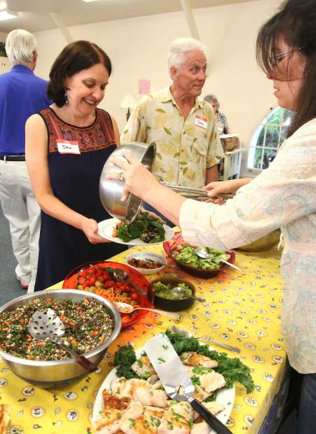 Rough and Ready's Dave and Debi Devitt smile as they are served dinner during Sierra Roots' Dare to Dream fundraising event for tiny homes for homeless.