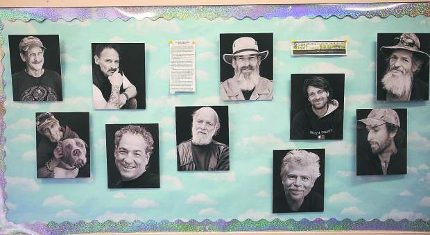 Photos of those that Sierra Roots serves, and wishes to build a tiny home community for, decorate the walls of Nevada City First Baptist Church where Saturday's Dare to Dream fundraiser was held.